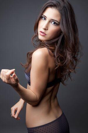 femme brune sexy: Jeune femme aux cheveux bouclés posant en lingerie Banque d'images