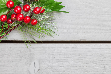 christmas  eve: Christmas decoration of holly springs on wooden background Stock Photo