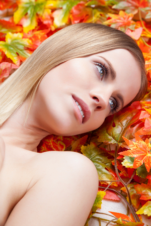 autumn leafs: Beautiful young woman lying on autumn leafs
