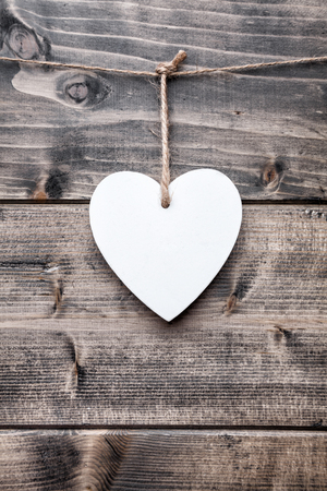 Love concept. Heart hanging on a string, shot on wooden background