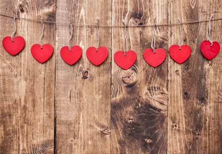Love concept. Hearts hanging on a string, shot on wooden background