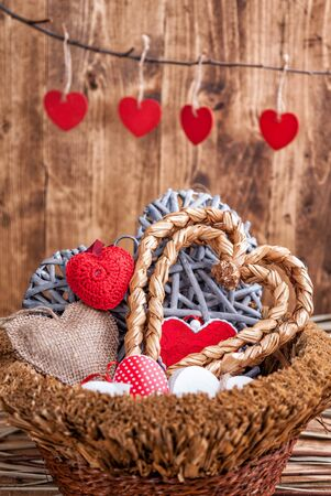 wooden basket: Many hearts inside an old wooden basket Stock Photo