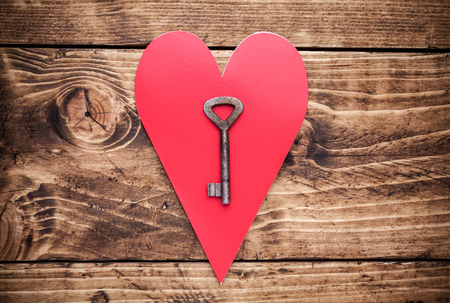 lock: Love concept. An Old key and a heart on wooden background Stock Photo