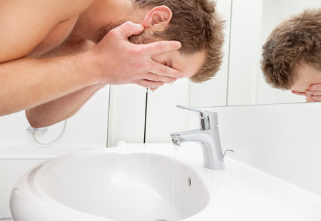 face cream: Man washing his face in the bathroom sink Stock Photo