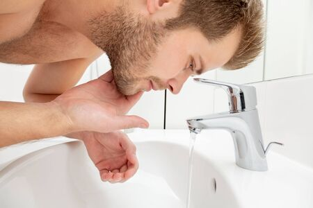 safe drinking water: Man washing his face in the bathroom sink Stock Photo