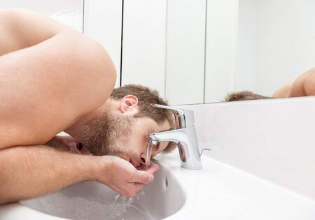 safe drinking water: Man drinks tap water from the bathroom sink