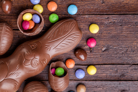 Delicious chocolate easter eggs and sweets on wooden background