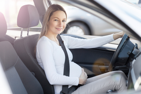 Donna incinta alla guida di un'auto, di indossare la cintura di sicurezza