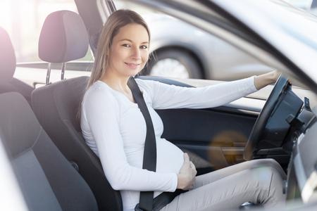 La mujer embarazada que conduce su coche, el uso del cinturón de seguridad