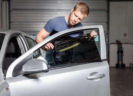 sunglight: Applying tinting foil onto a car window in a workshop