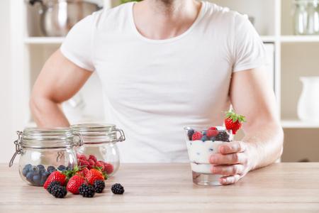 tomando jugo: el concepto de alimentación saludable. Primer en el hombre con un delicioso yogur con bayas frescas Foto de archivo