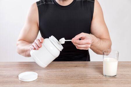vaso de leche: Primer en un hombre con suplementos nutiotion y proteínas en la mesa Foto de archivo