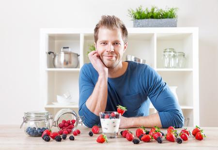 yogurt: el concepto de alimentación saludable. El hombre con un delicioso yogur con bayas frescas Foto de archivo