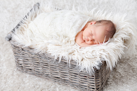 blanket: Beautiful newborn inside a wicker basket