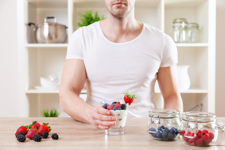 yaourt: concept de saine alimentation. L'homme avec un délicieux yogourt aux fruits frais