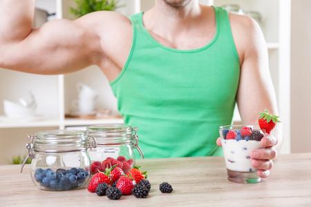 muscle training: Gesunde Ernährung Konzept. Der Mann mit leckeren Joghurt mit frischen Beeren