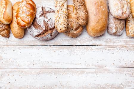 Delicioso pan recién horneado en el fondo de madera Foto de archivo