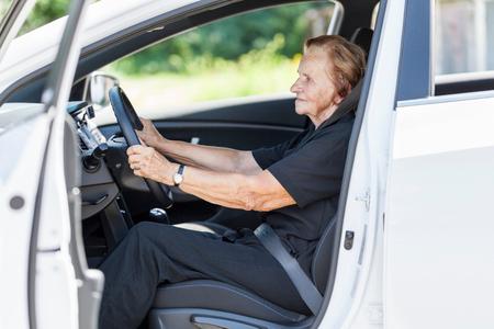 elderly woman: Elderly woman behind the steering wheel of a car Stock Photo