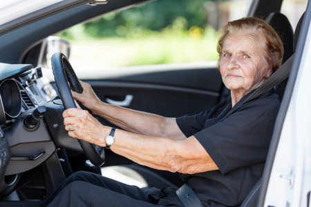 car wheel: Elderly woman behind the steering wheel of a car Stock Photo