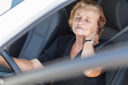 Elderly woman behind the steering wheel of a car Stock Photo