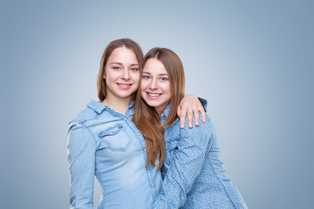 Studio portait of young and happy twin sisters embracing Stock Photo