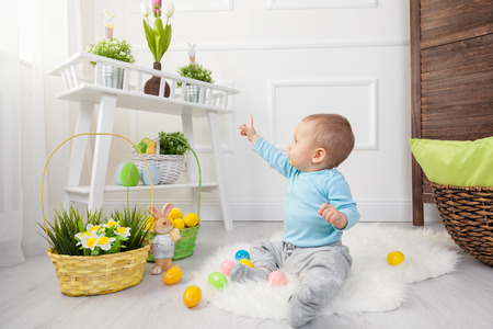 adorable child: Easter egg hunt. Adorable child playing with colorful Easter eggs at home