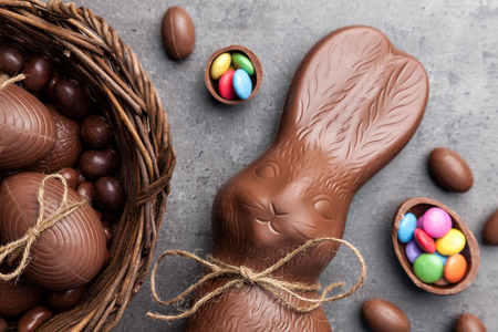 Delicious chocolate Easter bunny and eggs on wooden background Imagens