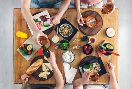 상위 뷰, 음식과 나무 테이블에 앉아있는 사람의 그룹, 음료를 즐기고 스톡 콘텐츠
