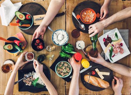 Draufsicht, Gruppe von Menschen sitzen am Holztisch mit Essen