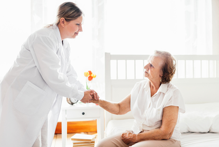 Providing care and support for elderly. Doctor visiting elderly patient at home. Stock Photo