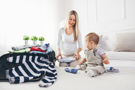 Travelling with kids. Happy mother with her child packing clothes for their holiday photo