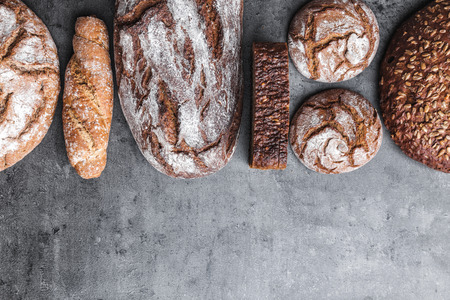 Delicious freshly baked brown bread on wooden background