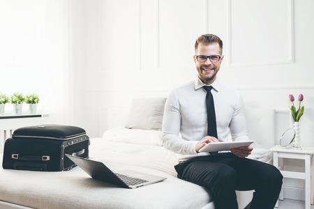 그의 호텔 방에서 태블릿 노트북으로 작동하는 침대에 젊은 사업가