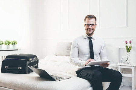Young businessman on bed working with a tablet laptop from his hotel room
