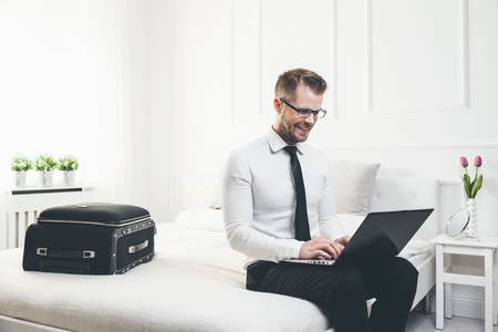 Young businessman on bed working with a laptop from his hotel room photo