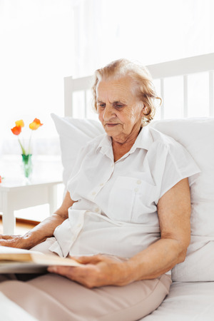 Elderly woman sitting comfortably in bed reading her favourite book at home