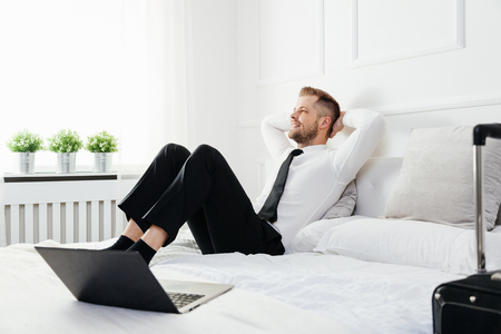 Young businessman relaxing on bed in his hotel room photo