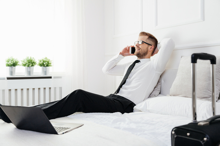 Young businessman working from a hotel room with his mobile phone photo