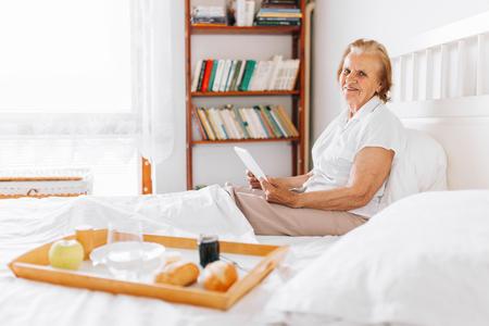 bedroom: Happy elderly woman having breakfast in bed whilst using her tablet Stock Photo