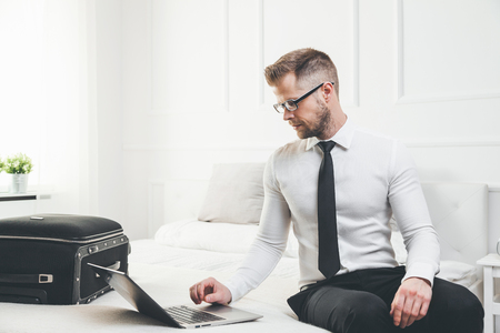 Young businessman working from a hotel room with his laptop photo