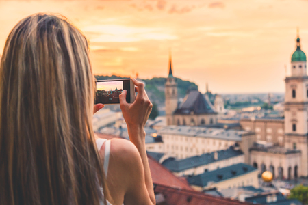 Tourist taking a photo with mobile of beatiful sunset in Salzburg Austria photo