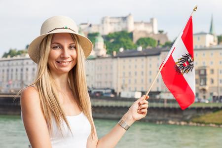 A female tourist on vacation in Salzburg Austria holding the Austrian flag photo