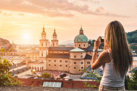 baroque: Tourist taking a photo with mobile of beatiful sunset in Salzburg Austria Stock Photo