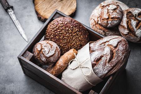 Ein Korb voller leckeren frisch gebackenen Brot auf Holzuntergrund Standard-Bild - 82773828