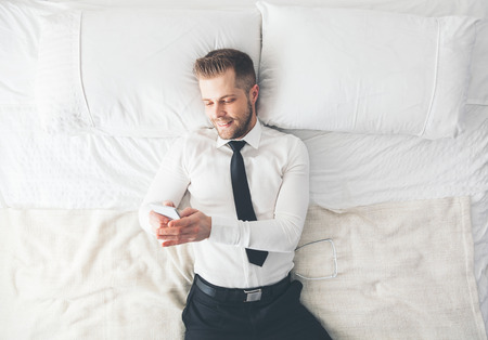Top view. Young handsome businessman lying on the bed texting from his smartphone photo