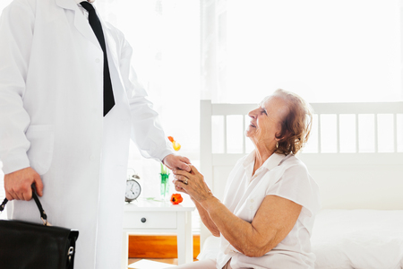 Providing care and support for elderly. Doctor visiting elderly patient at home. photo