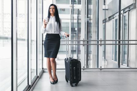 Erfolgreiche überzeugte junge Geschäftsfrau mit Kaffee und Koffer in einer Büroeinstellung