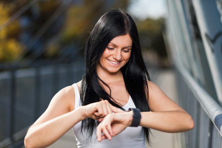 City workout. Beautiful young woman with a smartwatch training in an urban setting Stock Photo