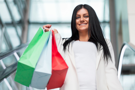 Beautiful young woman leaving the mall with plenty of shopping bags