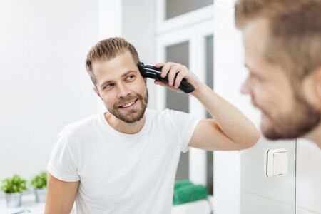 Handsome bearded man cutting his own hair with a clipper Stock Photo